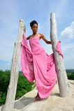 African American girl with dreadlocks posing on a high hill against the sky and a beautiful landscape. African American girl with dreadlocks, in a pink dress Stock Image
