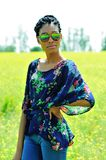 African American girl with dreadlocks, wearing sunglasses, standing in a field of yellow flowers on a Sunny day fnd smiles. African American girl with Stock Images