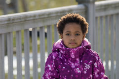 African-American girl in front of a fence. An young African-American girl wearing a winter coat and a hat Stock Photo