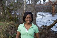 African American girl in front of river. An african-american girl standing in front of a river Royalty Free Stock Photo