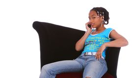 African American Girl Gossipin. Isolated african american girl sitting on the sofa and talking on the phone Stock Photos