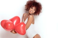 African american girl with heart shaped baloons. Stock Photo
