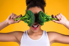 African American girl holding broccoli isolated. stock photo