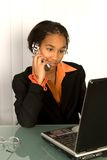 African-american girl with a laptop. African american girl working with phone and laptop Stock Photos