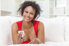 African American Girl Listening to MP3 Player Headphones. A beautiful mixed race African American girl or young woman laying down wearing a red dress listening Royalty Free Stock Photos