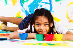 African american girl lying. Plastic jars with paints beside her Stock Image