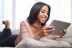 Teenage girl using digital tablet on sofa royalty free stock photos