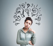 African American girl and multiple question marks on the wall Royalty Free Stock Image