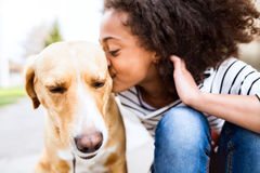 African american girl outdoors with her dog, kissing him. Beautiful african american girl with curly hair outdoors with her cute dog, kissing him Stock Images
