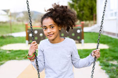 African american girl outdoors sitting on swing. Beautiful african american girl with curly hair outdoors wearing gray sweatshirt, sitting on swing royalty free stock images