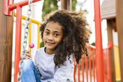 African american girl on playground eating lollipop. Royalty Free Stock Image