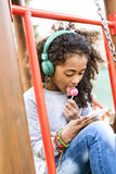 African american girl on playground with smart phone texting. Royalty Free Stock Photography
