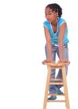 African American Girl Posing W. Isolated african american girl lean forward holding to wood bar stool stock photo
