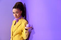 african american girl posing in yellow suit with purple apple, on trendy ultra royalty free stock images