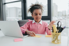 African american girl pretending to be businesswoman and working with laptop in office. Little african american girl pretending to be businesswoman and working Royalty Free Stock Images