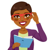 African American Girl Reading Book. Beautiful African American girl holding glasses and reading book happy smiling looking at front Royalty Free Stock Images