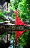 African American girl in a red dress with red shoes in hand is worth in the summer on the water on the stones in the Park. On a background of green plants and Stock Images