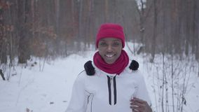 African american girl running through winter forest. Beautiful girl in warm jacket turns and looks in camera, smiling stock video