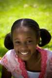 African-American Girl Smiling. A young african-american girl in the spring summer outdoors smiling Royalty Free Stock Images