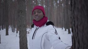 African american girl standing in winter forest, then turns and looks around with her hand on the tree. Beautiful girl stock video footage