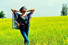 African American girl stands on the field with yellow flowers and looks at the sun. African American girl wearing sunglasses, jeans and a tunic, stands with his Royalty Free Stock Photography