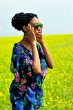 African American girl stands with his hands on the field with yellow flowers and looks away. African American girl wearing sunglasses, jeans and a tunic, stands Royalty Free Stock Image