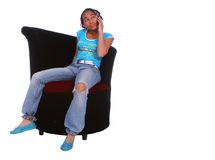 African American Girl Talking. Isolated african american girl sitting on the sofa and talking on the phone stock image