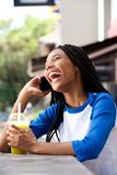 African american girl talking on mobile phone and laughing at cafe Stock Images