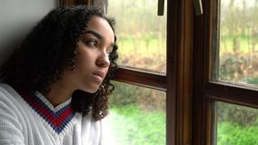 African American girl teenager depressed sitting by a window. Sad depressed beautiful mixed race African American girl teenager young woman wearing a white stock video