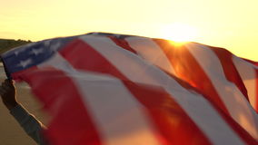 African American girl teenager female young woman on a beach holding an American US Stars and Stripes flag. 4K video clip of mixed race African American girl stock footage