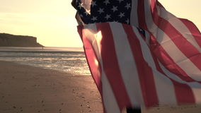 African American girl teenager female young woman on a beach wrapped in an American US Stars and Stripes flag. 4K desaturated video clip of mixed race African stock video footage