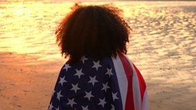 African American girl teenager female young woman on a beach wrapped in an American US Stars and Stripes flag. 4K video clip of mixed race African American girl stock footage