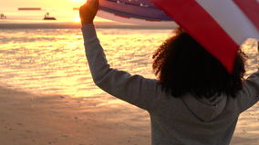 African American girl teenager female young woman on a beach wrapped in an American US Stars and Stripes flag. 4K video clip of mixed race African American girl stock video
