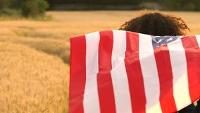 African American girl teenager female young woman holding an American USA Stars and Stripes flag in a wheat field at sunset or sun stock footage