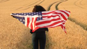 African American girl teenager female young woman holding an American USA Stars and Stripes flag in a wheat field at sunset or sun. 4K video clip of, mixed race stock footage