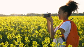 African American girl teenager female young woman taking photograph in field of yellow flowers stock video