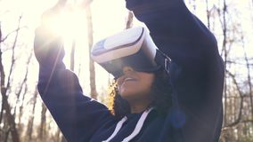 African American girl teenager female young woman using virtual reality VR headset in a forest woodland environment stock video footage