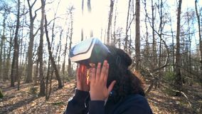 African American girl teenager female young woman using virtual reality VR headset in a forest woodland environment stock video