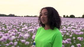 African American girl teenager female young woman walking through field of pink poppy flowers drinking water from a plastic bottle stock footage