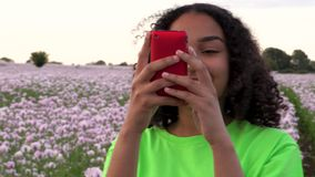 African American girl teenager female young woman walking through field of pink poppy flowers taking photographs for social media. Beautiful happy mixed race stock video footage