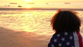 African American girl teenager female young woman wrapped in an American US Stars and Stripes flag on a beach. 4K video clip of mixed race African American girl stock video