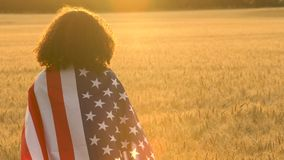 African American girl teenager female young woman wrapped in an American US Stars and Stripes flag. 4K video clip of mixed race African American girl teenager