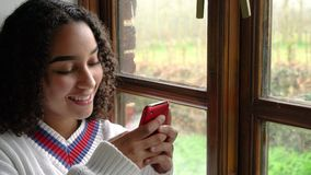 African American girl teenager sitting by a window using her mobile cell phone or smartphone. Happy smiling beautiful mixed race African American girl teenager stock video
