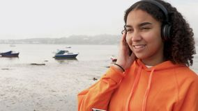 African American girl teenager young woman listening to music on wireless headphones using her smart cell phone. Follow shot video of beautiful mixed race stock footage