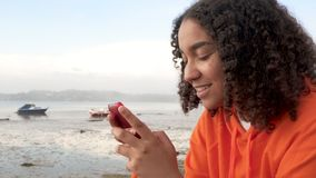 African American girl teenager young woman sitting on a sea front using her smart cell phone for social media or messaging. Beautiful happy mixed race African stock footage