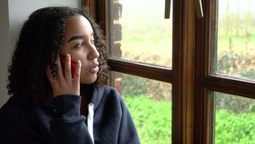 African American girl teenager young woman wearing a blue hoodie, sitting by a window talking on her mobile cell phone stock video footage