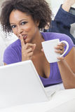 African American Girl Using Laptop Computer. A beautiful happy mixed race African American girl or young woman laying down on sofa using a laptop computer Royalty Free Stock Photo