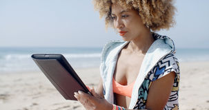 African American Girl Using Tablet Pc At Beach Stock Photo