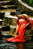 African American girl washes a dress in the water. African American girl in a red dress, with dreadlocks sitting in the summer on the rocks in the Park and Royalty Free Stock Photos