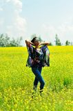 African American girl wearing sunglasses looking at the sun. African American girl wearing sunglasses, jeans and a tunic, standing in a field of yellow flowers Stock Photography